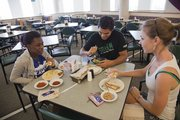 Freshman summer institute students Margo Dermey, Carlos Mendez and Christina Gelvin enjoy a lunch break in the dining area at the Ekdahl Dining Commons in Lewis Hall at Kansas University.