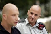 Israeli army Maj. Yoni Schoenfeld, right, listens to his partner, Noam, during an interview with the Associated Press in Tel Aviv, Israel.
