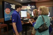 From left, Mark Lewis of the KU Bookstore tells incoming freshman Mallory Stevenson, 18, and her mother, Janet Stevenson, both of Leawood, some of the offerings the bookstore and KU have to offer to new students during a New Student Orientation session this summer. 