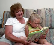 Anita Preston and her 5-year-old granddaughter Ashlyn Preston read a book at her home in Kennesaw, Ga., in this June 26 photo. Ashlyn is visiting from Florida to stay with her grandparents for the entire summer in lieu of day care or summer camp.