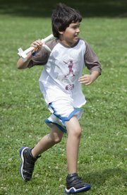A group of young NASA space campers learned about forces of flight and challenges of space travel at the South Park Recreation Center.  Eric Wheatman, 11, runs back holding a rocket stage that parachuted back to earth.