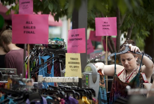 Above, Lawrence resident Emily Bayouth searches through a rack of dresses outside Creation Station during the 2009 Downtown Lawrence Sidewalk Sale.