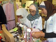 Parveen Razvi, left, and her friends Zoya Hamid, center, and Ambreen Zaidi, all of Canton, Mich., look over necklaces in the shop area during the Muslim Congress in Dearborn, Mich., in this July 4 photo.