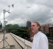 Wade McGillis, professor of Earth and Environmental Engineering at Columbia University, stands near his rooftop carbon dioxide monitor last month at an elementary school in the Harlem neighborhood of New York. Researchers are using the urban experiment to  track how much of the heat-trapping gas a city, neighborhood or building puts in the atmosphere, and how much the urban environment can suck out.