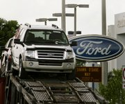 Ford vehicles are loaded onto a transporter outside a Ford dealership on Thursday in Miami Lakes, Fla. Helped by a lightened debt load, Ford Motor Co. posted a surprise second-quarter profit of $2.3 billion Thursday, following the worst loss in company history a year earlier.