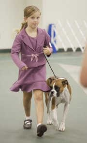 Tessa Gottstein, 9, Baldwin City, a member of the Palmyre 4-H club, runs her boxer, Meg, around the judging ring at the 4-H Dog Show on Saturday at the Douglas County Fairgrounds. Gottstein won a purple ribbon in level II showmanship.