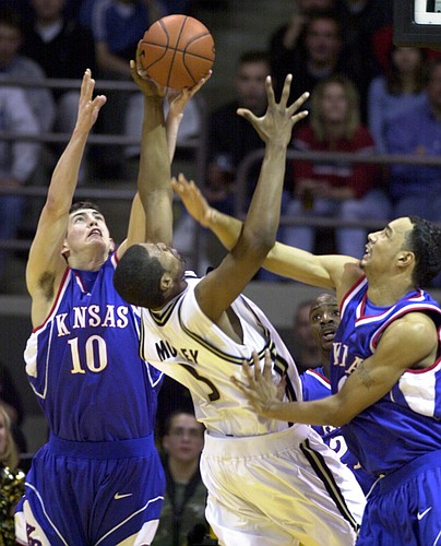 Kansas University players Kirk Hinrich, left, and Drew Gooden, try to steal the ball from Colorado's Jamahl Mosley. KU defeated Colorado, 84-69, to register the 1,700th victory in program history.