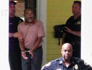 In this photo taken by a neighbor July 16, Harvard professor Henry Louis Gates Jr., center, is arrested at his home in Cambridge, Mass. Cambridge police officers attending include Sgt. James Crowley, right, and Sgt. Leon Lashley, front right.