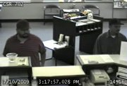 Two suspects in a stolen checks case are seen cashing the forged documents in a photo taken from a surveillance camera at First State Bank and Trust in Lawrence.