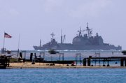 The USS Port Royal sits grounded atop a reef about a half-mile south of the Honolulu airport in this Feb. 6 photo. Hawaii plans to take the U.S. Navy to court to seek compensation for coral ruined when the Navy ship ran aground.