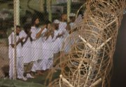 Guantanamo detainees pray before dawn near a fence of razor-wire, inside Camp 4 detention facility at Guantanamo Bay U.S. Naval Base, Cuba, in this May 14 photo. Several senior U.S. officials said the administration is eyeing a soon-to-be-shuttered state maximum security prison in Michigan and the military penitentiary at Fort Leavenworth as possible locations for a heavily guarded site to hold the 229 suspected al-Qaida, Taliban and foreign fighters now jailed at Guantanamo Bay.