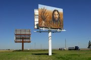 A painting of Jesus in a wheatfield hangs along Interstate 70 last month in Colby. Tuffy and Linda Kay Taylor erected the billboard for Colby residents and motorists who travel down Interstate 70 at all hours of the day and night.