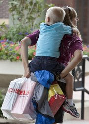 A shopper carries her child and shopping bags July 28 in Omaha, Neb. It's still early, but analysts' grades already are coming in: the back-to-school shopping season is off to a lousy start.