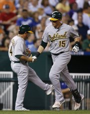 Oakland's Ryan Sweeney (15) is congratulated by third-base coach Mike Gallego after hitting a home run in the eighth inning. The A's beat the Royals, 9-4, Friday in Kansas City, Mo.