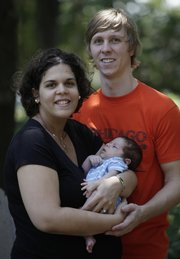 Jay and Megan Mkrtschjan hold their month-old son, Seth, on Aug. 3 in Wheaton, Ill. The Mkrtschjans decided to marry early, despite pressure from family, colleagues and some Christian groups to delay marriage.