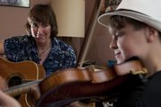 Instructor Diane Gillenwater goes over playing style with her young pupil Ethan Rhodes. The 12-year-old musician will be one of several players in the youth division at the Kansas State Fiddling and Picking Championships.