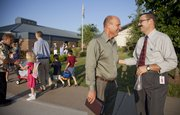 Prairie Park School principal David Williams, far right, greets new Lawrence school superintendent Rick Doll on the first day of school Aug. 12, 2009. Doll just completed his first year as USD 497 superintendent.