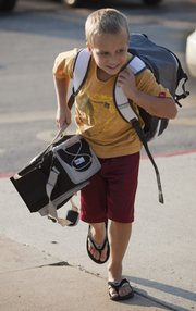 Under the weight of two backpacks, Alden Hunt races to the doors of Prairie Park School in this 2009 photo.