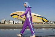 Sama Wareh walks along the sand dressed in swimwear designed for Muslim women Newport Beach, Calif., in this Feb.15, 2007, file photo. A French Muslim was denied entry to a swimming pool for wearing an Islamic-style full-body swimsuit.