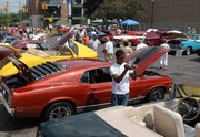 Car enthusiasts enjoy the show during the annual Dream Cruise, which spans a 16-mile stretch along Woodward Ave., Saturday in Ferndale, Mich. Automakers might be suffering, but for just a day, it looks like the glory days of car culture are back again in Michigan.