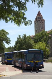 Bus drivers await passengers near Dyche Hall on Kansas University's campus. Changes to the transit system permit city residents with a T pass to ride campus buses, while KU students with a pass can ride the T.