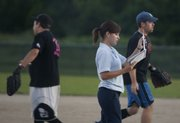 Umpire Lauren Trower, Lawrence, reads over the score sheet in between innings.