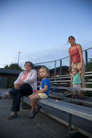 Three generations of softball supporters watch Casey Lee of Lawrence from the bleachers. From left are Casey Lee's mother, Mary Lee, Lawrence; daughter Maya, 3; wife, Amy Lee; and daughter Cami, 1.