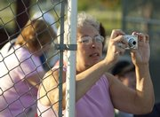 Lenette Hamm, Lawrence, composes a photo as she watches Those Sons of Pitches at the Clinton Lake Softball Complex.