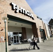 A shopper leaves a T.J. Maxx store Feb. 21, 2007, in Framingham, Mass. Discount retail operator TJX Cos. on Tuesday said its fiscal second-quarter profit rose 31 percent as its stores like T.J. Maxx and Marshalls continued to lure in cost-conscious shoppers.