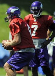 Minnesota Vikings quarterback Brett Favre (4) works out during training camp on Tuesday in Eden Prairie, Minn. Teammate Tarvaris Jackson (7) is looking on.