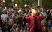 Fire eater Rod Sipe entertains the masses gathered at the corner of Ninth and Massachusetts streets during opening night of the Lawrence Busker Festival on Friday. In addition to the flames, visitors were treated to magic tricks and music on the streets of downtown. More than 20 performers from all over the country will be performing throughout the weekend.