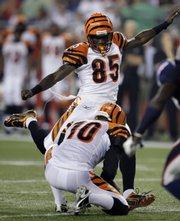 Cincinnati Bengals wide receiver Chad Ochocinco kicks an extra point Thursday in Foxborough, Mass. Holding is punter Kevin Huber.