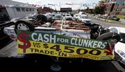 A Cash for Clunkers sign hangs on an upside-down automobile Friday at a dealership in Detroit. The Obama administration will bring to an end the popular $3 billion Cash for Clunkers program on Monday, giving car shoppers a few more days to take advantage of big government incentives.
