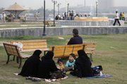 An Iraqi family picnics Friday in a park in the Azamiyah neighborhood in north Baghdad. The normally bustling streets of Baghdad are subdued, in sharp contrast to the lively atmosphere that had returned as major violence ebbed over the past two years.