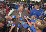 Kansas football coach Mark Mangino signs autographs for fans. Mangino spoke to fans at the KU Football Kickoff in September 2009 in Prairie Village.