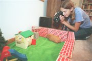 Alyssa Buecker, shown Jan. 7, 1999, in her Lawrence home, films her guinea pigs. Here, Little Angel, left, and Dolly are in a backyard setting.