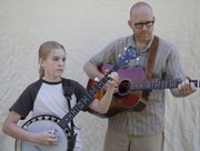 Jai Strecker, 11, and her father, Stu Strecker, Lawrence, practice a banjo tune before the banjo competition at the Kansas State Fiddling and Picking Championships.