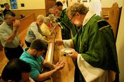 The Rev. Paul K. McLain gives communion to parishioners at the Solemn High Mass at Trinity Episcopal Church, 1011 Vt.
