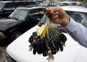 Keys to clunkers are held up by sales manager Mark Hranicky at a lot where nearly 90 cars were traded in over the past few weeks during the government's Cash for Clunkers program in Topsham, Maine. Monday was the final day for the program.