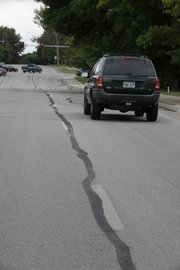 Crews this summer poured a sealer in the cracks of pavement all over town. As this fix in the 800 block of Kasold Drive shows, the sealant sometimes interferes with lane striping and other pavement markings that help drivers keep their bearings.