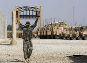 a U.S. soldier carries a bed frame in Camp Carver on the outskirts of Madain, Iraq, about 15 miles southeast of Baghdad, in this May 27 file photo. The U.S. military is packing up to leave Iraq in what has been deemed the largest movement of manpower and equipment in modern military history, shipping out more than 1.5 million pieces of equipment from tanks to antennas along with a force the size of a small city.