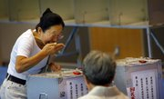 A woman reacts as she casts her vote in Japan's parliamentary elections today at a polling station in Tokyo.