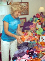 Kay Self, of Newton, sorts through a pile of donated flip- flops bound for Haiti in this Aug. 19 photo. Self has received more than 500 pairs of flip flops and shoes that she will distribute as a part of a mission trip next month. Until then, they are piled up in her Newton home's spare bedroom.