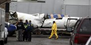 Wreckage from a plane crash is loaded onto a flatbed trailer for removal in this Feb. 18 file photo at the scene where Continental Flight 3407 crashed into a home in Clarence, N.Y. NTSB's investigation of the crash of the flight, killing 50, has spotlighted the long hours, low pay and long-distance commutes of regional airline pilots.
