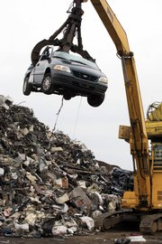 "A crane lifts a discarded vehicle to a shredder at Gershow Recycling Corp. in this Aug. 6 file photo in Medford, N.Y. A Fed survey found Wednesday that the majority of regions reported that the government's Cash for Clunkers program ""boosted traffic and sales."" But aside from brisk businesses at auto dealerships, other merchants struggled."