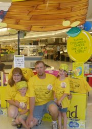 Kara and Todd Cunningham of Baldwin City along with their children, Lane and Lakin, volunteer at Alex's Lemonade Stand in June at the Hy-Vee store on Sixth Street. Lane, who is in remission after battling neuroblastoma, will be among the children attending the Heroes and Halos event Saturday in Eudora.