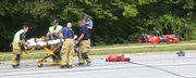 Lawrence Douglas County Fire and Medical personnel get ready to transport a motorcyclist who hit the rear of a car at St. Andrews Drive and Bob Billings Parkway about 2 p.m Friday. The motorcyclist was flown by Life Star helicopter to a regional trauma center.