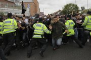 British police officers try to control anti-fascist protesters as they charge against anti-Muslim protesters in the London suburb of Harrow on Friday.