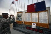 A U.S. soldier photographs names of Pentagon casualties during a ceremony to mark the anniversary of Sept. 11 at the main U.S. base in Bagram, north of Kabul, Afghanistan, on Friday. A wave of violence has spread through the country the last two days, killing more than 50 people.