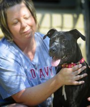 Angie Cartwright holds her dog, Lucey, in this Aug. 31 photo in Salina. Cartwright chose to have her dog DNA tested to determine her heritage after the dog was mistaken for a pit bull.